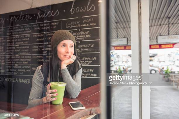 Caucasian woman drinking smoothie in cafe