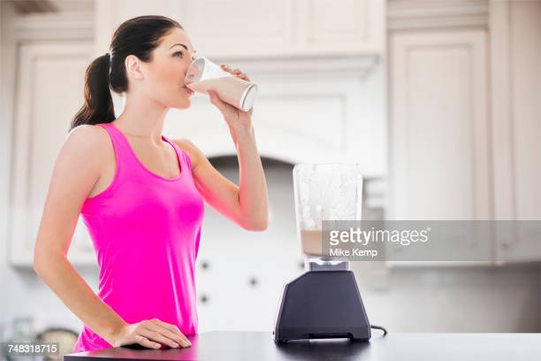 caucasian woman drinking smoothie in kitchen - protein drink stock pictures, royalty-free photos & images