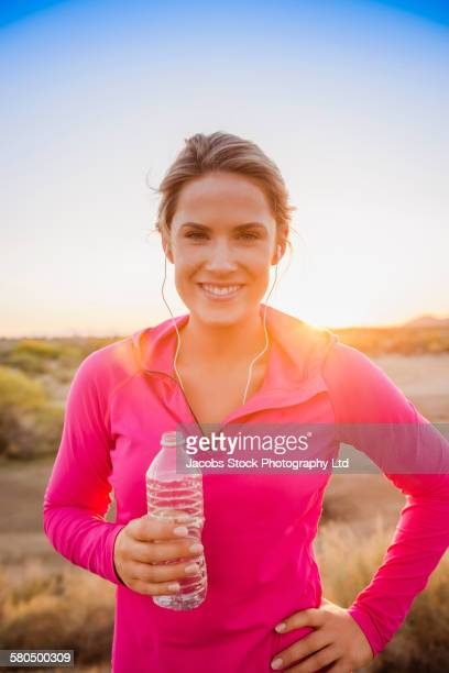 Caucasian woman drinking water bottle in remote field