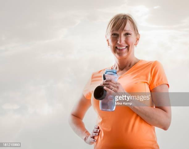Caucasian woman drinking water bottle