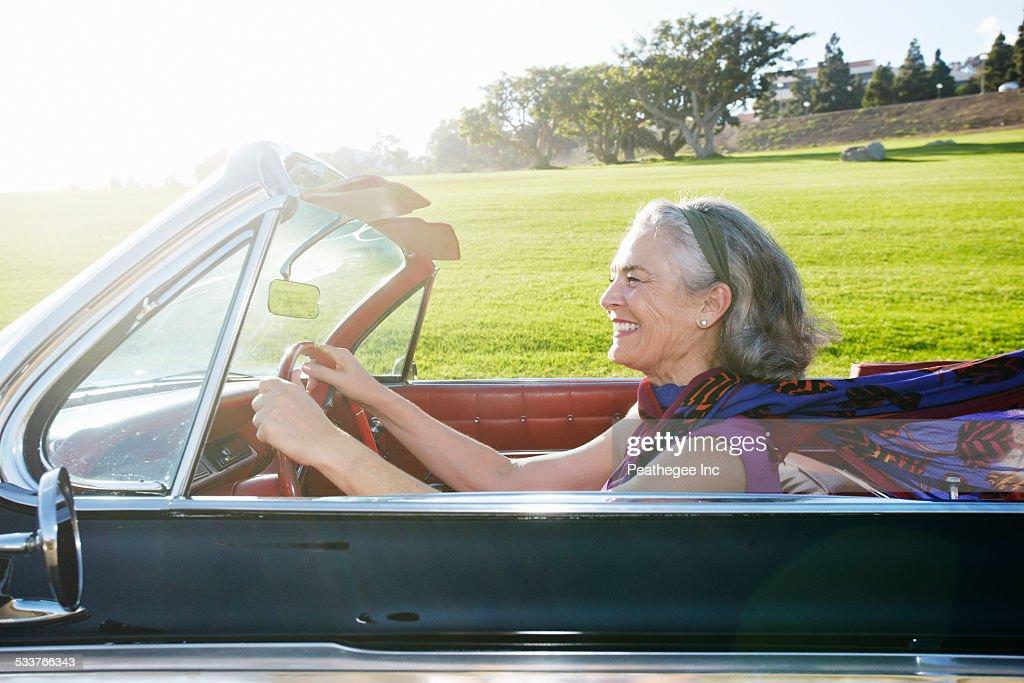 Caucasian woman driving classic convertible : Foto stock