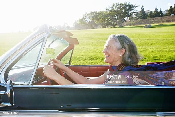 Caucasian woman driving classic convertible