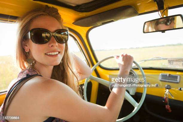 Caucasian woman driving old-fashioned car