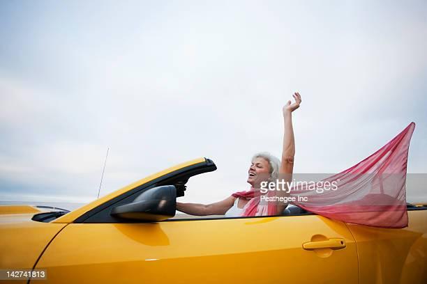 Caucasian woman driving yellow convertible