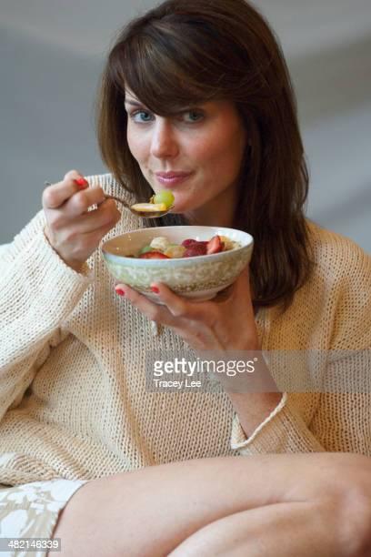 Caucasian woman eating bowl of fruit