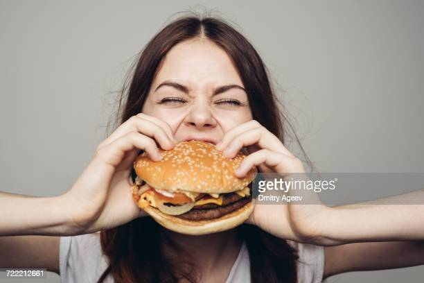 Caucasian woman eating cheeseburger