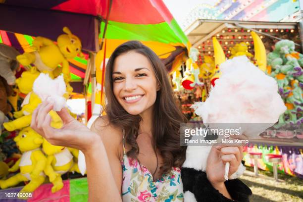 Caucasian woman eating cotton candy at carnival