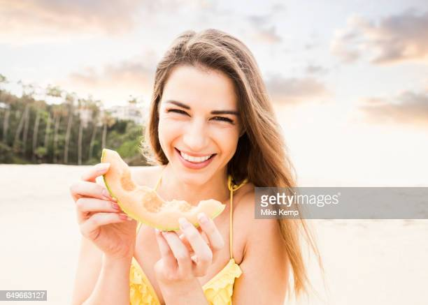 Caucasian woman eating fruit on beach
