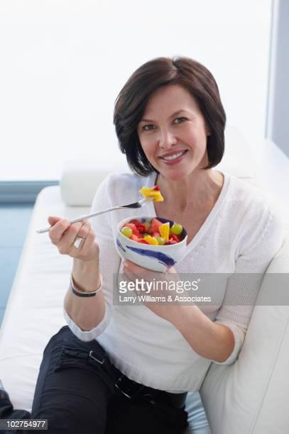 Caucasian woman eating fruit salad