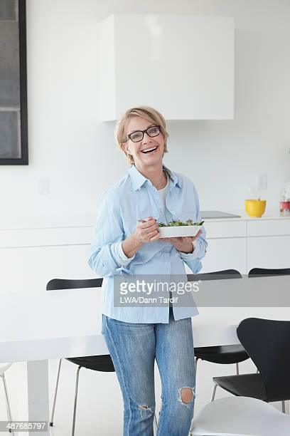 Caucasian woman eating in kitchen