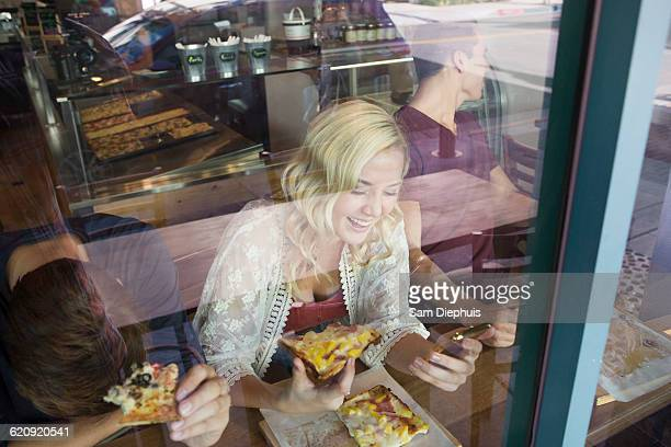 Caucasian woman eating pizza in cafe