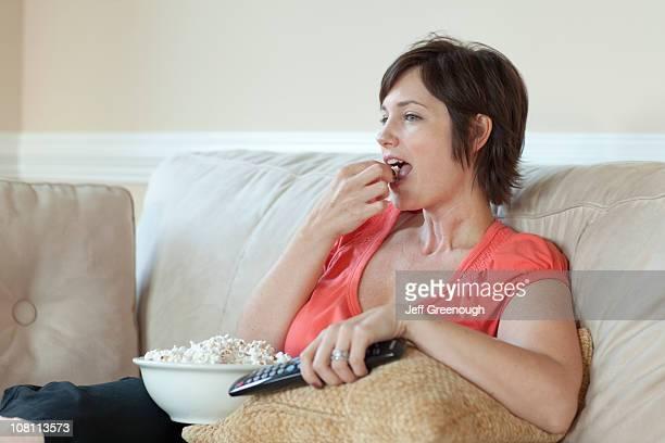 europäischer abstammung frau essen popcorn und vor dem fernseher - frauen über 30 stock-fotos und bilder