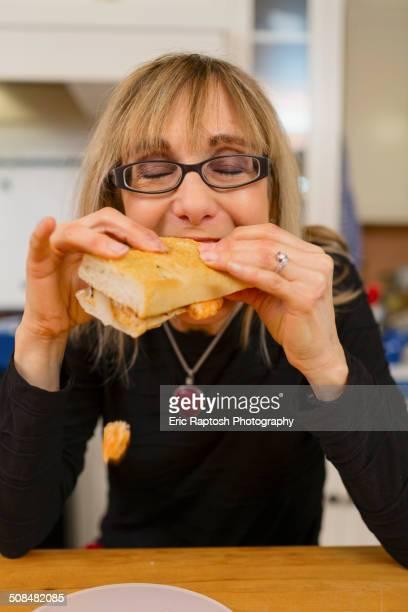 Caucasian woman eating sandwich in kitchen