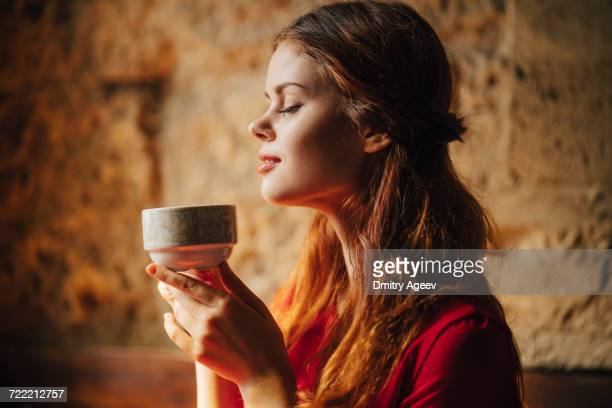 Caucasian woman enjoying aroma of cup of tea