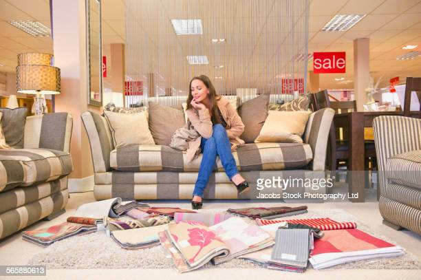 Caucasian woman examining fabric swatches in furniture store