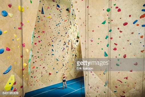 Caucasian woman examining indoor rock wall