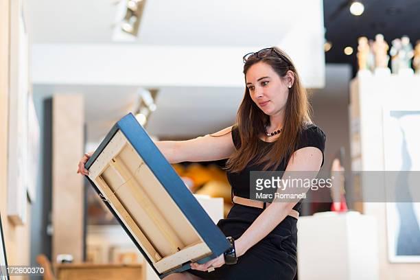 Caucasian woman examining painting in art gallery