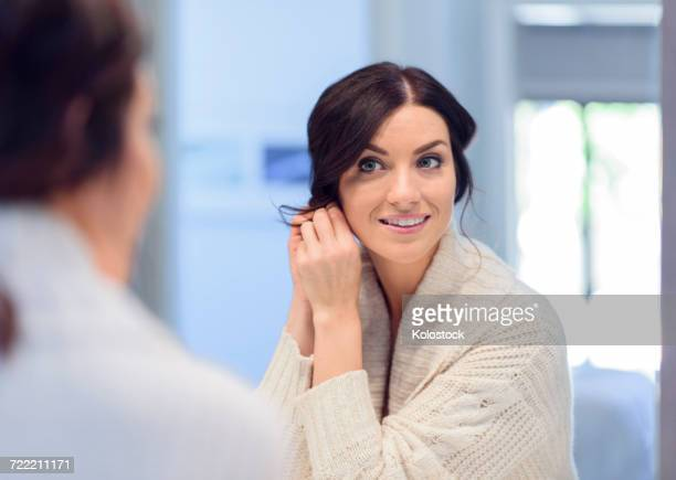 caucasian woman fastening earring in mirror - ohrring stock-fotos und bilder
