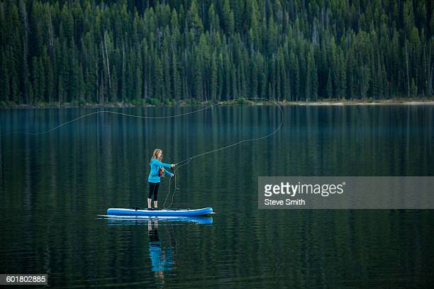 caucasian woman fishing from paddle board in river - sun valley idaho stock photos and pictures