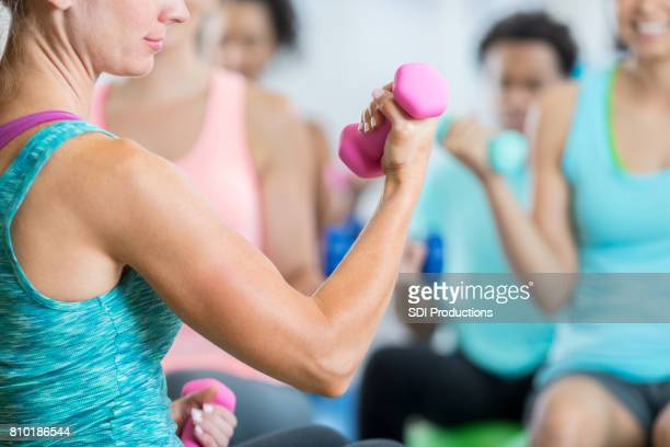 Caucasian woman flexes biceps while lifting hand weight