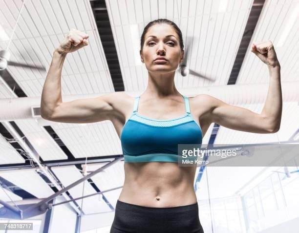 caucasian woman flexing arm muscles - adulto de idade mediana - fotografias e filmes do acervo