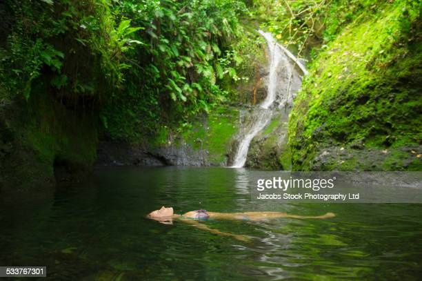 Caucasian woman floating in remote jungle pool
