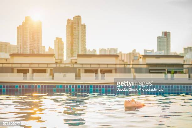 Caucasian woman floating in urban rooftop swimming pool, Singapore