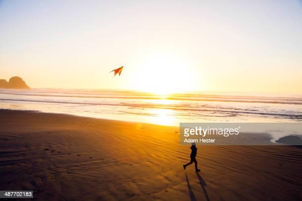 Caucasian woman flying kite on beach