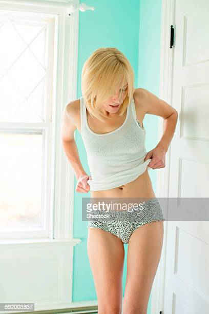 Caucasian woman getting dressed in bedroom