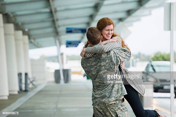 Caucasian woman greeting soldier boyfriend