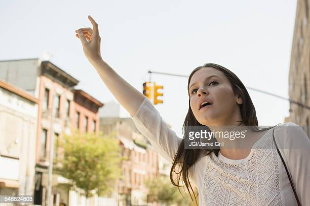 Caucasian woman hailing taxi in city