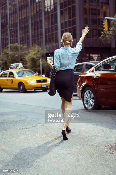 caucasian woman hailing taxi in urban street - back to work stock pictures, royalty-free photos & images