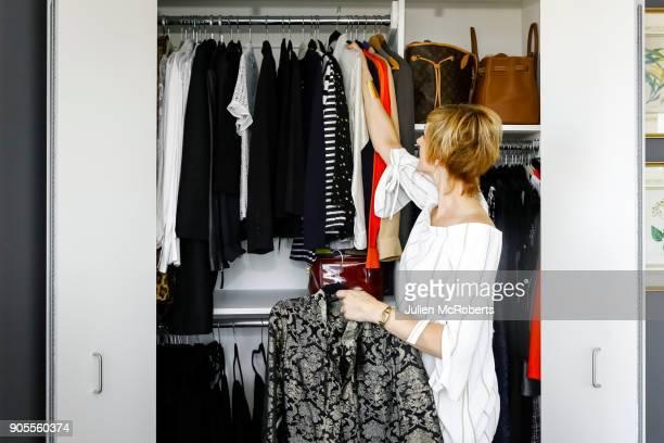 caucasian woman hanging clothes in closet - kast stockfoto's en -beelden