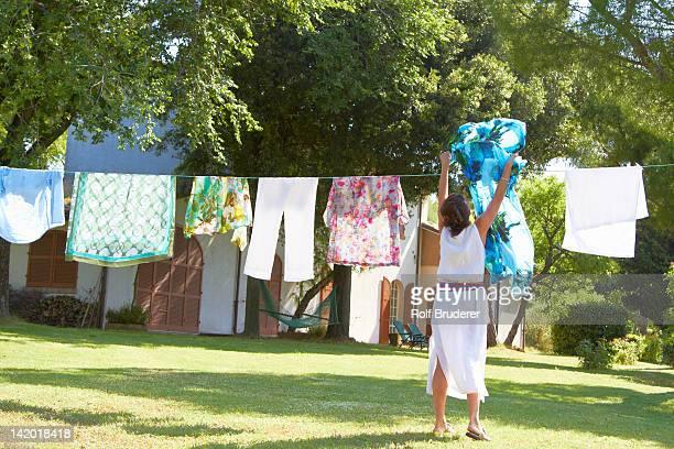 caucasian woman hanging laundry on clothes line - 物干し ストックフォトと画像