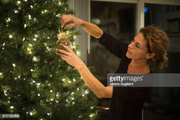 Caucasian woman hanging ornament on Christmas tree