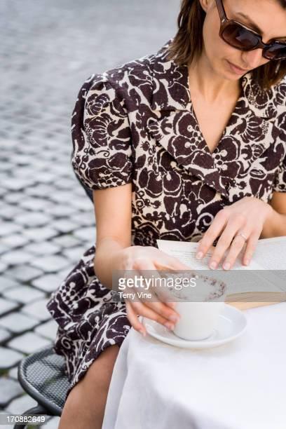 Caucasian woman having coffee at sidewalk cafe