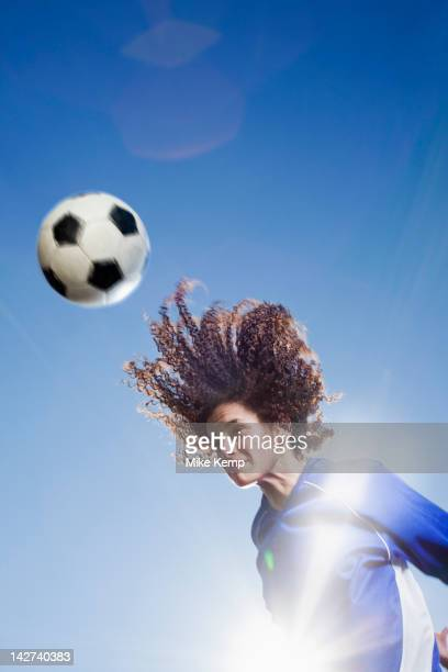 Caucasian woman heading soccer ball