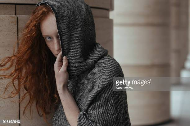 caucasian woman hiding face behind hood - hood clothing stock photos and pictures