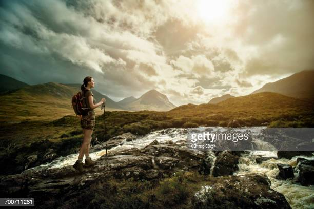 Caucasian woman hiking on rocks near river