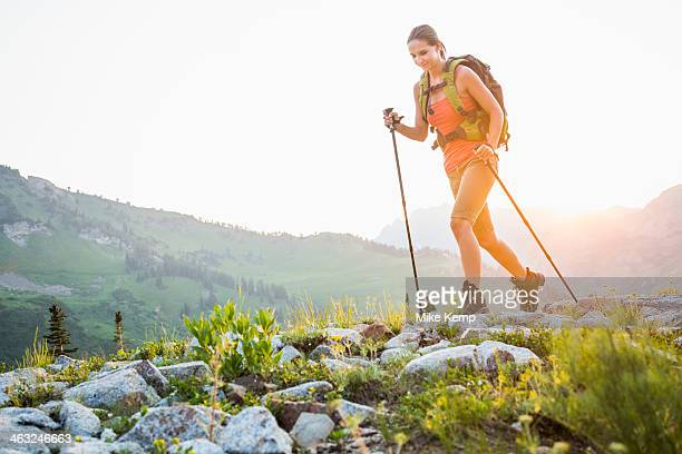 caucasian woman hiking on rocky trail - stick stock-fotos und bilder
