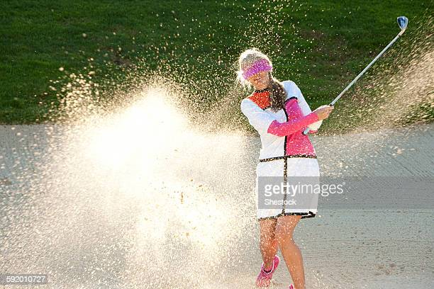 caucasian woman hitting golf ball in sand trap while blindfolded - バンカー ストックフォトと画像