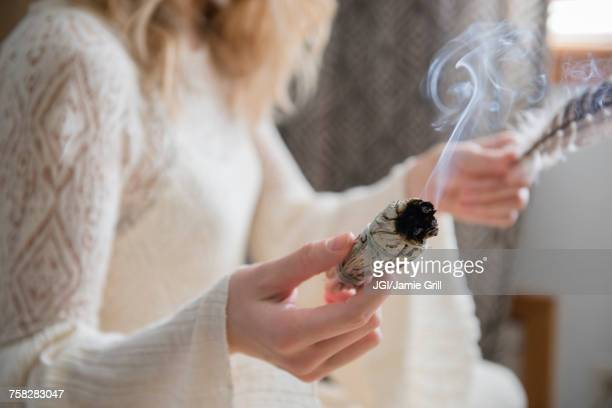 caucasian woman holding a feather and ritual incense - incense stock photos and pictures