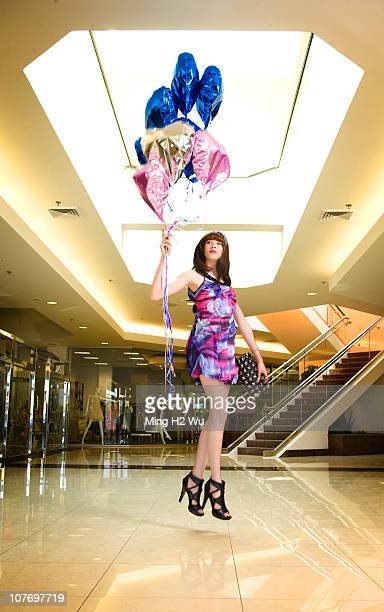 Caucasian woman holding balloons floating in mid-air