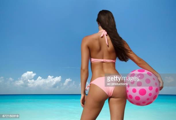 Caucasian woman holding beach ball at ocean