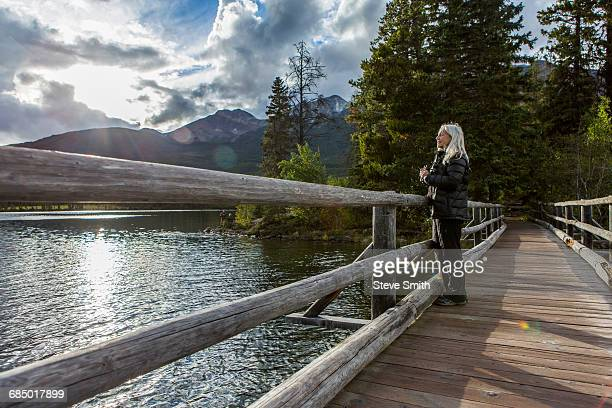 Caucasian woman holding binoculars at mountain lake