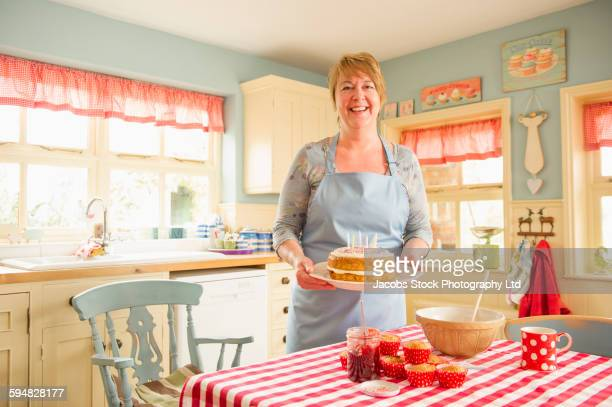 Caucasian woman holding birthday cake in kitchen