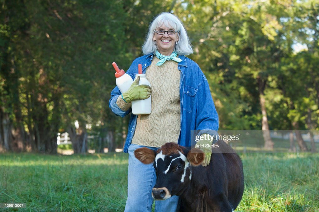 Caucasian woman holding bottles and petting calf : Stock Photo