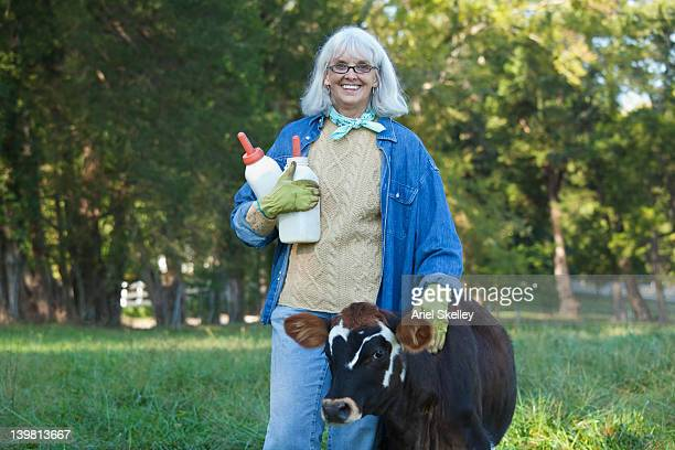Caucasian woman holding bottles and petting calf