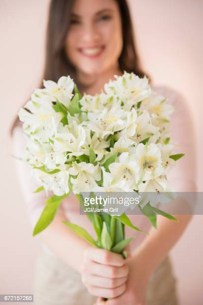 Caucasian woman holding bouquet of white flowers