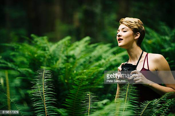 Caucasian woman holding camera in forest